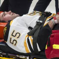 Photo - Boston Bruins' Johnny Boychuk is carried off the ice after taking a hit from Montreal Canadiens' Max Pacioretty during first period NHL hockey action Thursday, Dec. 5, 2013 in Montreal. (AP Photo/The Canadian Press, Paul Chiasson)