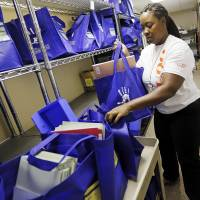Photo - Volunteer Christy Davison loads a cart with bags of school supplies  at the Foundation for Oklahoma City Public Schools. The foundation, through its Teachers Warehouse program, recently reached the $1 million mark for giving away school supplies. Photo by Nate Billings, The Oklahoman  NATE BILLINGS - THE OKLAHOMAN