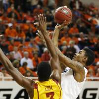 Photo - Oklahoma State guard Le'Bryan Nash, right, shoots in front of Iowa State forward Melvin Ejim during the first half of an NCAA college basketball game in Stillwater, Okla., Wednesday, Jan. 30, 2013. (AP Photo/Sue Ogrocki)