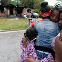 Photo - Sisters Brandy McCrary, left, and Breona Montgomery, who are cousins of the five fatal house fire victims, hug neighbors Bonita Beasley, center, and Jennifer Moss, right, in Newnan, Ga., Saturday, April 27, 2013.  The fire killed Alonna T. McCrary, 27, as well as her 5-year-old daughter Eriel McCrary and 2-year-old daughter Nikia White, according to Glenn Allen, the Georgia state Insurance commissioner's spokesman. Two other children, Messiah White, 3, and McKenzie Florence, 2, also died. Allen said the two were sleeping over at the home. A fifth child, 11-year-old Nautica McCrary, escaped the burning home and was taken to a hospital to be treated for smoke inhalation. (AP Photo/David Tulis)