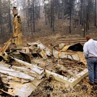 Photo - U.S. Sen. Jon Tester, D-Mont., looks at the remains of a Lolo Creek home that was destroyed by the West Fork II fire when it swept down the Lolo Creek canyon, Wednesday, Aug. 21, 2013 near Lolo, Mont. The fire burned four other homes as well along the U.S. Highway 12 corridor. (AP Photo/Missoulian, Kurt Wilson)