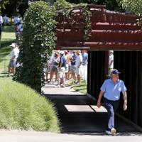 Photo - Colin Montgomerie walks through a bridge made out of an old railroad box car during the second round of the U.S. Senior Open golf tournament at Oak Tree National in Edmond, Okla., Friday, July 11, 2014. (AP Photo/Sue Ogrocki)