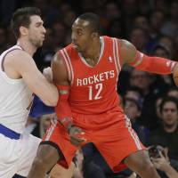 Photo - New York Knicks' Andrea Bargnani, left, of Italy, defends Houston Rockets' Dwight Howard during the first half of an NBA basketball game Thursday, Nov. 14, 2013, in New York. (AP Photo/Frank Franklin II)