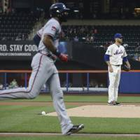 Photo - Atlanta Braves' Jason Heyward, left, runs toward home plate after hitting a solo home run off New York Mets starting pitcher Zack Wheeler, right, in the first inning of a baseball game, Wednesday, Aug. 27, 2014, in New York. (AP Photo/John Minchillo)