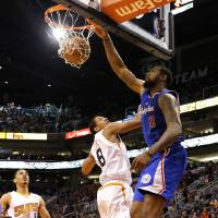 Photo - Los Angeles Clippers center DeAndre Jordan (6) dunks over Phoenix Suns forward Channing Frye (8) during the first half of an NBA basketball game on Wednesday, April 2, 2014, in Phoenix. (AP Photo/Matt York)