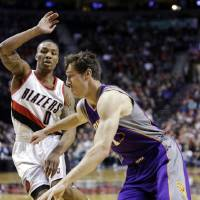 Photo - Phoenix Suns guard Goran Dragic, right, of Slovenia, drives on Portland Trail Blazers guard Damian Lillard during the first quarter of an NBA basketball game in Portland, Ore., Tuesday, Feb. 19, 2013. (AP Photo/Don Ryan)