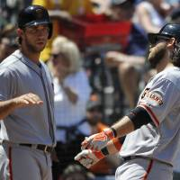 Photo - San Francisco Giants' Brandon Crawford, right, is congratulated on his solo home run by teammate Madison Bumgarner during the fourth inning of a baseball game on Sunday, May 4, 2014, in Atlanta. (AP Photo/David Tulis)