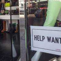 Photo - In this  Friday, Dec. 7, 2012, photo, a help wanted sign is posted on the front window of a clothing boutique in Los Angeles.The number of Americans seeking unemployment benefits fell sharply for a fourth straight week, a sign that the job market may be improving. The Labor Department said Thursday, Dec. 13, 2012, that weekly applications for unemployment benefits fell 29,000 last week to a seasonally adjusted 343,000, the lowest in two months. It is the second-lowest total this year.  (AP Photo/Damian Dovarganes)