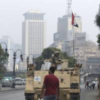 Photo - An Egyptian walks in front of an army armored vehicle that guards an entrance of Tahrir Square, in Cairo, Egypt, Friday, Aug. 16, 2013. Egypt is bracing for more violence after the Muslim Brotherhood called for nationwide marches after Friday prayers and a