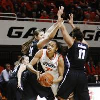 Photo - Oklahoma State's Kendra Suttles (31) splits Kansas State defenders Chantay Caron (11) and Ashlynn Knoll (21) during an NCAA girl's college basketball game between Oklahoma State University (OSU) and Kansas State at Gallagher-Iba Arena in Stillwater, Okla., Saturday, March 1, 2014. Oklahoma State defeated Kansas State in 67-62. Photo by KT King, The Oklahoman