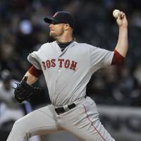 Photo - Boston Red Sox starter Jon Lester delivers a pitch during the first inning of a baseball game against the Chicago White Sox in Chicago, Thursday, April 17, 2014. (AP Photo/Paul Beaty)