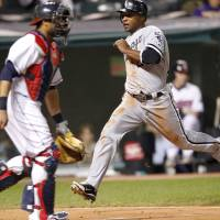 Photo -   Chicago White Sox's Dewayne Wise, right, scores on a single by designated hitter Adam Dunn in the sixth inning of a baseball game against the Cleveland Indians, Monday, Oct. 1, 2012, in Cleveland. Indians catcher Carlos Santana, left, watches. (AP Photo/Tony Dejak)