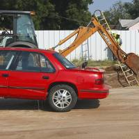Photo - A car is towed away after being removed from a sinkhole that formed when a water main broke at NW 2nd and Villa in Oklahoma City, Thursday, Sept. 5, 2013. Photo by Nate Billings, The Oklahoman