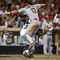 Photo - St. Louis Cardinals' Matt Carpenter attempts to avoid the tag by San Diego Padres catcher Rene Rivera while trying to score from third on an infield grounder by Matt Holliday in the fifth inning of a baseball game Tuesday, July 29, 2014, in San Diego. Carpenter was out on the play. (AP Photo/Lenny Ignelzi)