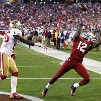 Photo - Arizona Cardinals wide receiver Andre Roberts (12) pulls in a touchdown pass as San Francisco 49ers cornerback Tramaine Brock defends during the second half of an NFL football game, Sunday, Dec. 29, 2013, in Glendale, Ariz.  (AP Photo/Ross D. Franklin)