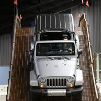 Photo - Erin O'Connor drives a Jeep Wrangler through the obstacle course of Camp Jeep at the Oklahoma City International Auto Show at State Fair Park.  Steve Gooch - The Oklahoman