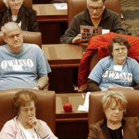 Photo - Owasso residents Frank and Sandra Wall listen to lawmakers on the House floor Monday during Senior Day at the state Capitol in Oklahoma City. Photo By Steve Gooch, The Oklahoman