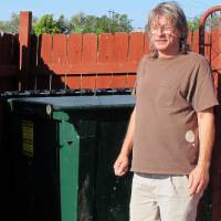 Photo - Ralph Smith, a maintenance worker at the Legacy Inn & Suites, stands in front of the trash bin Tuesday where he found discarded bomb-making materials in Miami, OK. Smith reported the find to authorities last week, and they later arrested Gregory Arthur Weiler II for possession of an explosive device. AP Photo  Justin Juozapavicius