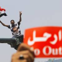 Photo - An opponent of Egypt's Islamist President Mohammed Morsi shouts slogans during a protest in Tahrir Square in Cairo, Egypt, Wednesday, July 3, 2013. A Defense Ministry official said army chief Gen. Abdel-Fattah el-Sissi is meeting with his top commanders, hours before the military's deadline to the president and opposition to resolve the nation's political crisis is set to expire. Arabic read