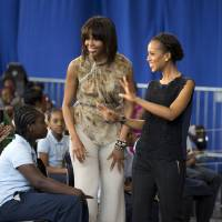 Photo - First lady Michelle Obama and actress Kerry Washington smile as they arrive for a performance at Savoy Elementary School in Washington, Friday, May 24, 2013. The Savoy School was one of eight schools selected last year for the Turnaround Arts Initiative at the President's Committee on the Arts and Humanities.  Turnaround Arts Schools use the arts as a central part of their reform strategy to improve low performing schools  (AP Photo/Evan Vucci)