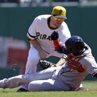Photo - Pittsburgh Pirates second baseman Neil Walker, top, tags out Atlanta Braves' Ramiro Pena who was attempting to steal second during the first inning of a baseball game in Pittsburgh, Sunday, April 21, 2013. (AP Photo/Gene J. Puskar)