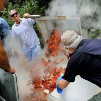 Photo -  Volunteers Max Martin, right, and Joe Ballard, background, empty a basket of cooked crawfish into a container to be taken to the serving area at Yukon's Chisholm Trail Crawfish Festival. Photo by Jim Beckel, The Oklahoman   Jim Beckel -