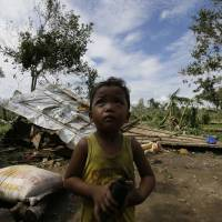 Photo - A child stands near his family's damaged house Wednesday Dec. 5, 2012, a day after powerful Typhoon Bopha hit Montevista township Compostela Valley in southern Philippines. Typhoon Bopha, one of the strongest typhoons to hit the Philippines this year, barreled across the country's south on Tuesday, killing scores of people while triggering landslides, flooding and cutting off power in two entire provinces. (AP Photo/Bullit Marquez)