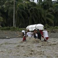 Photo - Relatives cross a river to bury their loved one, who died in a flash flood caused by Typhoon Bopha, Thursday, Dec. 6, 2012, in New Bataan township, Compostela Valley in southern Philippines.  The powerful typhoon that washed away emergency shelters, a military camp and possibly entire families in the southern Philippines has killed hundreds of people with nearly 400 missing, authorities said Thursday. (AP Photo/Bullit Marquez)