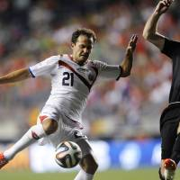 Photo - Costa Rica's Marco Urena (21) takes a shot on goal as Ireland's Richard Keogh defends during the second half of an international friendly soccer match on Friday, June 6, 2014, in Chester, Pa. The match ended in a 1-1 tie. (AP Photo/Michael Perez)