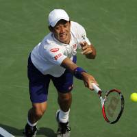 Photo - Kei Nishikori, of Japan, lunges for the ball against Sam Querrey during a match at the Citi Open tennis tournament, Wednesday, July 30, 2014, in Washington. (AP Photo/Nick Wass)