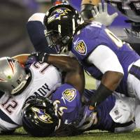 Photo -   New England Patriots quarterback Tom Brady (12) is sacked by Baltimore Ravens linebacker Dannell Ellerbe (59) in the first half of an NFL football game in Baltimore, Sunday, Sept. 23, 2012. Also pictured tackling Brady is Ravens linebacker Courtney Upshaw. (AP Photo/Nick Wass)