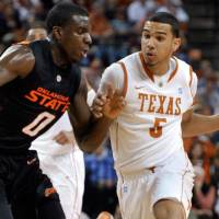 Photo - Texas guard Cory Joseph, right, drives around Oklahoma State forward Jean-Paul Olukemi during the first half of an NCAA college basketball game Wednesday, Feb. 16, 2011, in Austin, Texas. (AP Photo/Michael Thomas)