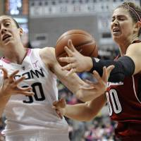 Photo - Connecticut's Breanna Stewart, left, and Louisville's Sara Hammond, right, reach for a loose ball during the first half of an NCAA college basketball game on Sunday, Feb. 9, 2014, in Storrs, Conn. (AP Photo/Jessica Hill)