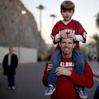 Photo - Craig Logsdon carries his seven-year-old son Jude Logsdon, from Scottsdale but originally from Guthrie, to the Insight Bowl college football game between the University of Oklahoma (OU) Sooners and the Iowa Hawkeyes at Sun Devil Stadium in Tempe, Ariz., Friday, Dec. 30, 2011. Photo by Bryan Terry, The Oklahoman