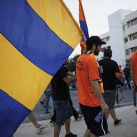 Photo - Fans of Cyprus soccer team APOEL hold flags of their team as they take part in a demonstration outside of the Cyprus Football Association in capital Nicosia, Cyprus, Tuesday, May 27, 2014. Hundreds of APOEL fans have staged a peaceful protest outside the Cyprus Football Association's headquarters over a decision to replay the season's abandoned final soccer match between the Nicosia team and rival AEL Limassol that would have decided the championship. (AP Photo/Petros Karadjias)