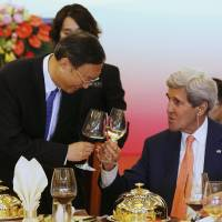 Photo - China's State Councillor Yang Jiechi, left, shares a toast with U.S. Secretary of State John Kerry before a working lunch at the U.S.-China Strategic and Economic Dialogue, at the Diaoyutai State Guesthouse in Beijing Wednesday, July 9, 2014. (AP Photo/Jim Bourg, Pool)