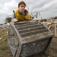 Photo -  Left: Heather Smith, of Dallas, a member of Mormon Helping Hands, rolls an air-conditioning unit across a yard at a home in Moore on May 27, 2013. Photo by K.T. King, The Oklahoman Archives   KT King -