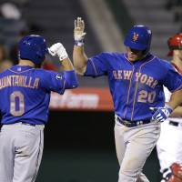 Photo - New York Mets' Anthony Recker (20) celebrates his home run with Omar Quintanilla during the 13th inning of a baseball game against the Los Angeles Angels on Saturday, April 12, 2014, in Anaheim, Calif. (AP Photo/Jae C. Hong)