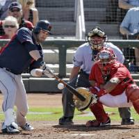 Photo - Cleveland Indians' Jason Kipnis hits a three-run home run off Cincinnati Reds relief pitcher J.J. Hoover as Reds' catcher Brayan Pena and home plate umpire D.J. Reyburn watch  in the sixth inning of a spring exhibition baseball game Monday, March 24, 2014, in Goodyear, Ariz. (AP Photo/Mark Duncan)