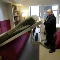Photo - Jack Sproule tries out a fold-down bed in a 325 square foot model apartment at an exhibit called