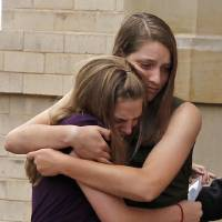 Photo -   Mourners hold onto each other as they depart a memorial service for Gordon Cowden Wednesday, July 25, 2012 in Denver. Cowden was one of 12 people killed, and over 50 wounded in a shooting attack early Friday at the packed theater during a showing of the Batman movie,