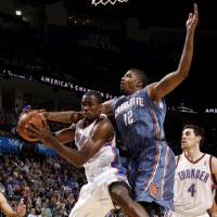 Photo - Oklahoma City's Serge Ibaka (9) grabs a rebound beside Charlotte's Tyrus Thomas (12) during an NBA basketball game between the Oklahoma City Thunder and the Charlotte Bobcats at the Oklahoma City Arena, Friday, March 18, 2011. Photo by Bryan Terry, The Oklahoman