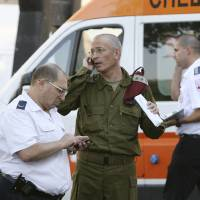 Photo -   Israeli military and medical personnel talk in front of a hospital in the city of Burgas, Bulgaria, Thursday, July 19, 2012. A daytime bombing that killed eight people and injured dozens on a bus full of Israeli tourists was most likely a suicide attack, Bulgaria's interior minister said Thursday. He said the suspected attacker was carrying a Michigan driver's license that was being sent to the FBI for authentication. (AP Photo/Impact Press Group)