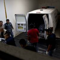 Photo -   Morgue employees remove the bodies of people who were killed by an explosion at a gas pipeline distribution center in Reynosa, Mexico, near Mexico's border with the U.S., Tuesday Sept. 18, 2012. Mexico's state-owned oil company says at least five people are still listed as missing in a pipeline fire that killed over 20 workers and injured over 40 others on Tuesday. (AP Photo/Hans-Maximo Musielik)