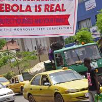 Photo - A banner reading 'Ebola is real, Protect yourself and your family', warns people of the Ebola virus in Monrovia, Liberia, Saturday Aug. 2, 2014. An Ebola outbreak that has killed more than 700 people in West Africa is moving faster than efforts to control the disease, the head of the World Health Organization warned, as presidents from the affected countries met Friday in Guinea's capital. (AP Photo/Abbas Dulleh)