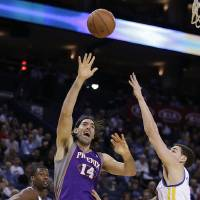 Photo - Phoenix Sun's Luis Scola (14) shoots against Golden State Warriors' Klay Thompson, right, during the first half of an NBA basketball game Wednesday, Feb. 20, 2013, in Oakland, Calif. (AP Photo/Ben Margot)