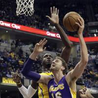 Photo - Los Angeles Lakers center Pau Gasol, of Spain, right, shoots in front of Indiana Pacers center Roy Hibbert during the first half of an NBA basketball game in Indianapolis, Tuesday, Feb. 25, 2014. (AP Photo/AJ Mast)