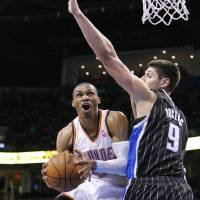 Photo - Oklahoma City Thunder guard Russell Westbrook, left, goes to the basket around Orlando Magic center Nikola Vucevic, right, during the third quarter of an NBA basketball game in Oklahoma City, Friday, March 15, 2013. Oklahoma City won 117-104.  (AP Photo/Alonzo Adams)
