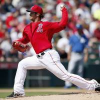 Photo - Los Angeles Angels' C.J. Wilson throws a pitch against the Kansas City Royals during the first inning of a spring training baseball game Friday, March 21, 2014, in Tempe, Ariz. (AP Photo/Ross D. Franklin)