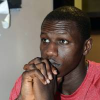 Photo - Louisville center Gorgui Dieng watches a broadcast of the women's team playing Connecticut in the NCAA Final Four college basketball tournament championship game in New Orleans, Tuesday, April 9, 2013, at Cluckers Bar in Louisville, Ky. (AP Photo/Timothy D. Easley)